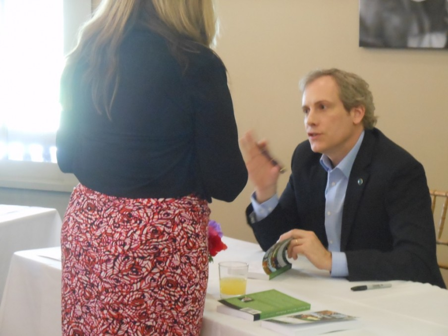 Chris signing a copy of 100 MILES for a reader at the Junior League of Poughkeepsie Authors' Luncheon.